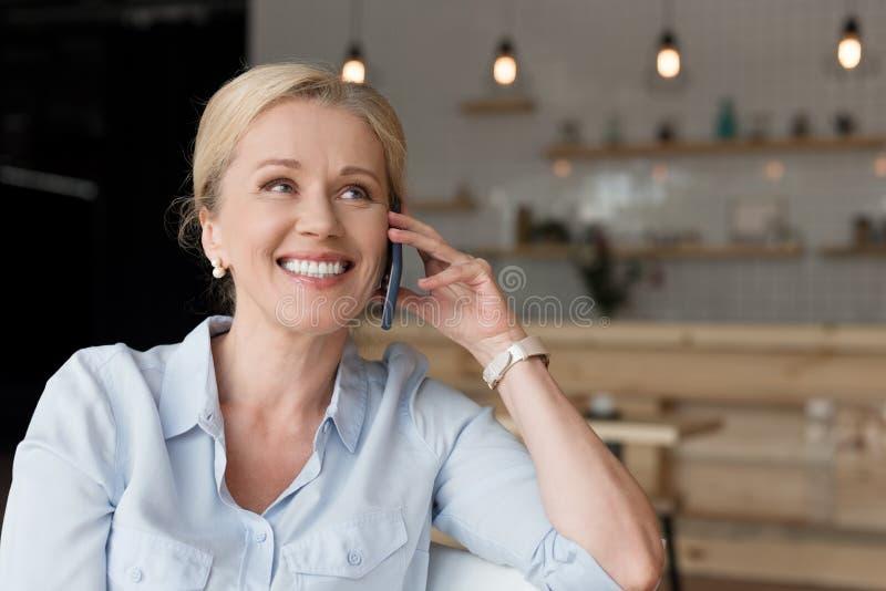 gladlynt mogen kvinna som talar på smartphonen och bort ser royaltyfri foto