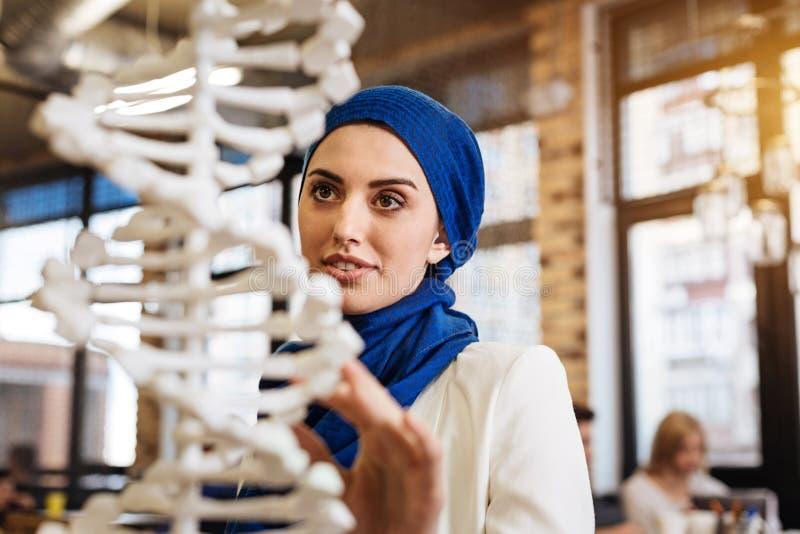 Gladlynt nyfiken muslimkvinna som studerar genomics royaltyfri bild