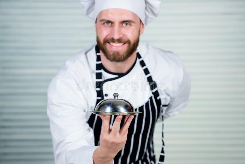 Gladlynt och artigt restaurangmaterial Tjänande som mål för ledar- kock i restaurang Kockkock i likformign som står med arkivfoton
