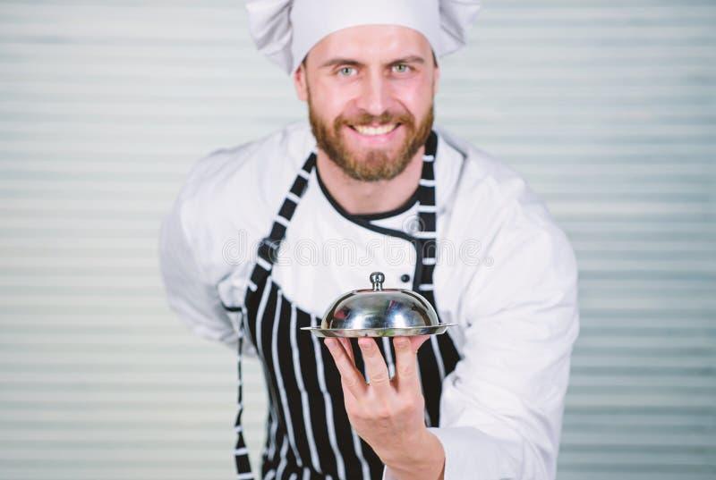 Gladlynt och artigt restaurangmaterial Tj?nande som m?l f?r ledar- kock i restaurang Kockkock i likformign som st?r med royaltyfri fotografi