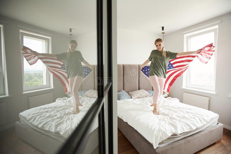 Gladlynt patriot med amerikanska flaggan som firar självständighetsdagen royaltyfri foto