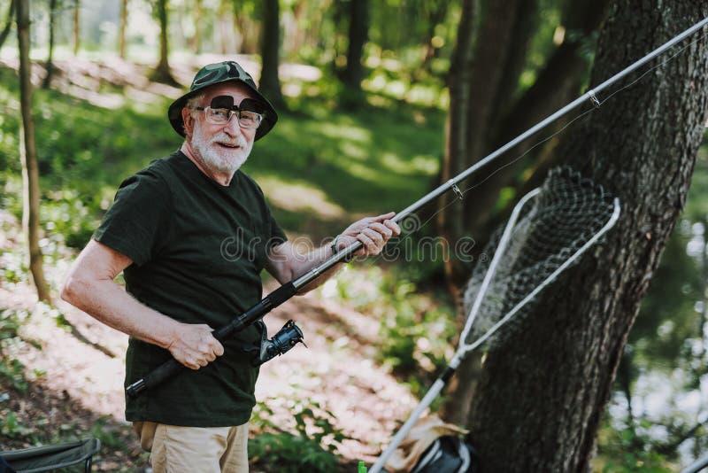 Gladlynt pensionerad man som tycker om fiskeaktivitet med nöje royaltyfri foto