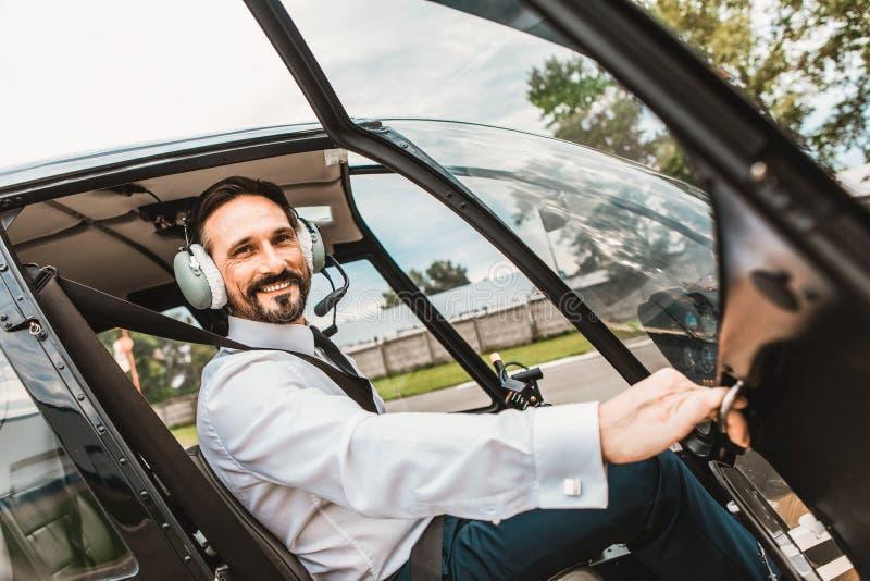 Gladlynt pilot som öppnar dörren av hans kabin och le royaltyfri bild