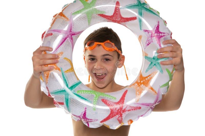 Gladlynt pojke i badskyddsglasögon och med en uppblåsbar cirkel i hans händer, skratt och blickar till och med cirkeln, begrepp a royaltyfri bild