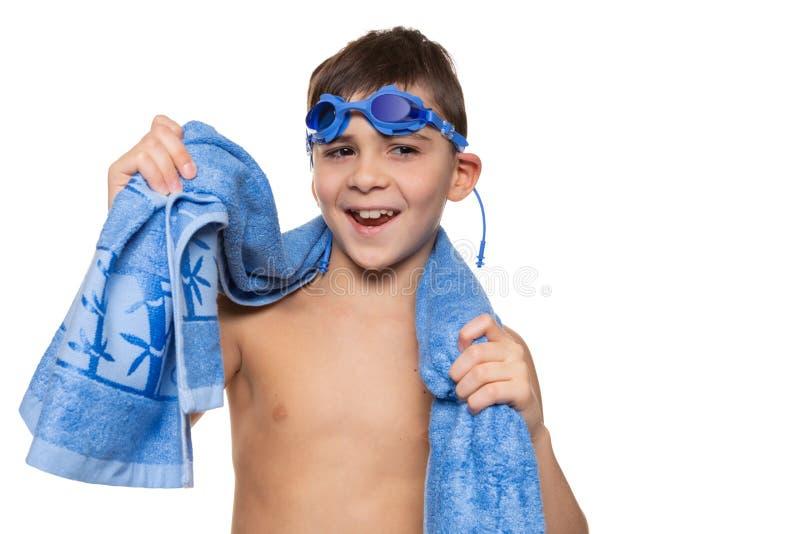 Gladlynt pojke, med blå simma skyddsglasögon på hans huvud och med en blå handduk på hans skuldror, skratt, begrepp, på en vit royaltyfri bild