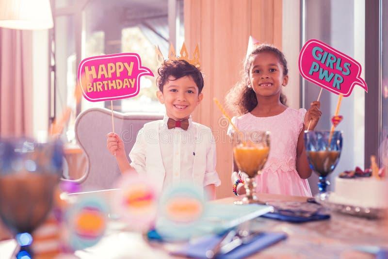 Gladlynt pojke som rymmer tecknet för lycklig födelsedag, medan stå nära flickan royaltyfria bilder