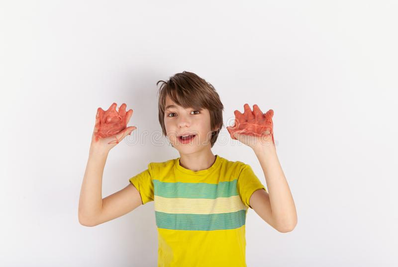 Gladlynt pojke som visar slam på hans händer arkivfoton