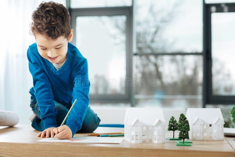 Gladlynt pojkesammanträde på tabellen och teckningen royaltyfria foton