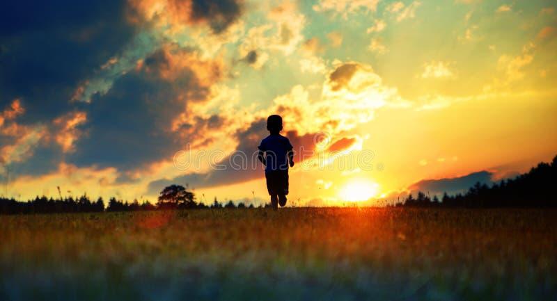 Gladlynt pojkespring in mot solnedgången royaltyfri foto
