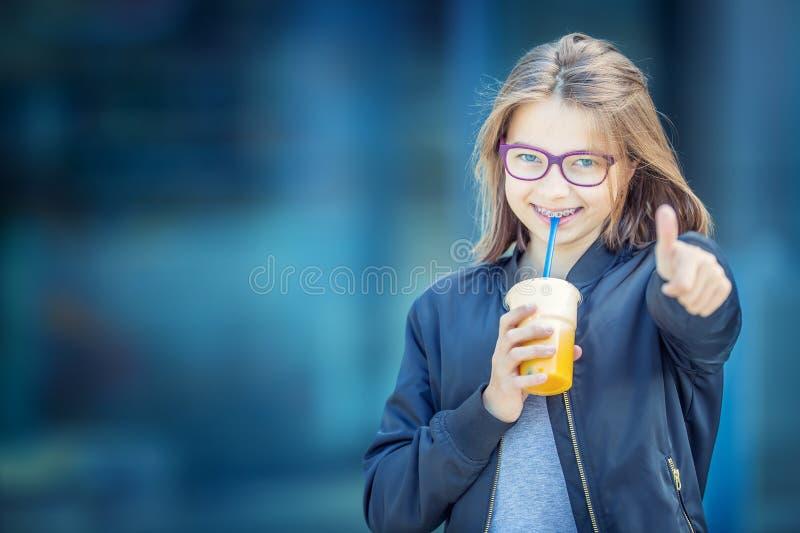 Gladlynt pre-tonårs- flicka som dricker fruktsaft Flicka med tand- tandhänglsen och exponeringsglas fotografering för bildbyråer