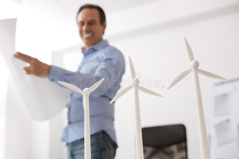 Gladlynt professioanlengineeer som är involverad i projekt för vindturbin arkivfoto