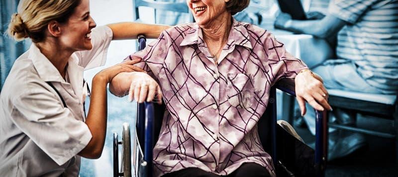 Gladlynt rörelsehindrat högt kvinnasammanträde på rullstolen som ser den kvinnliga doktorn royaltyfri bild