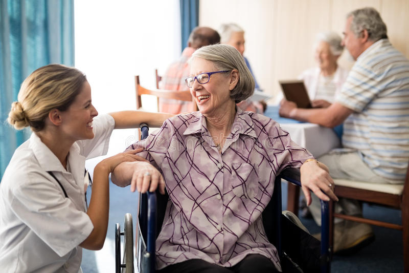 Gladlynt rörelsehindrat högt kvinnasammanträde på rullstolen som ser den kvinnliga doktorn arkivfoton