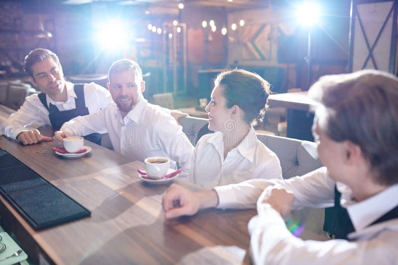 Gladlynt restaurangpersonal som pratar och dricker kaffe efter wor arkivbilder