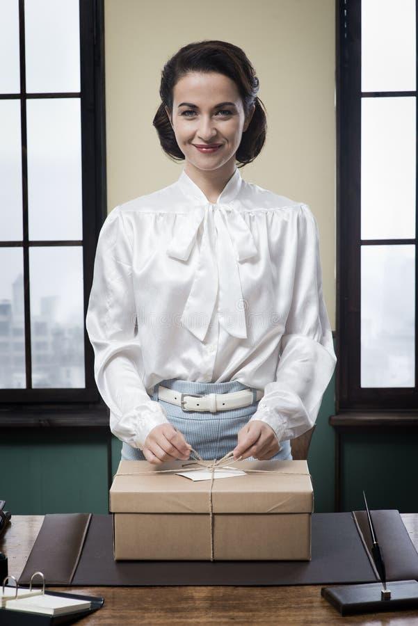 Gladlynt sekreterare som rymmer en postpacke royaltyfria bilder