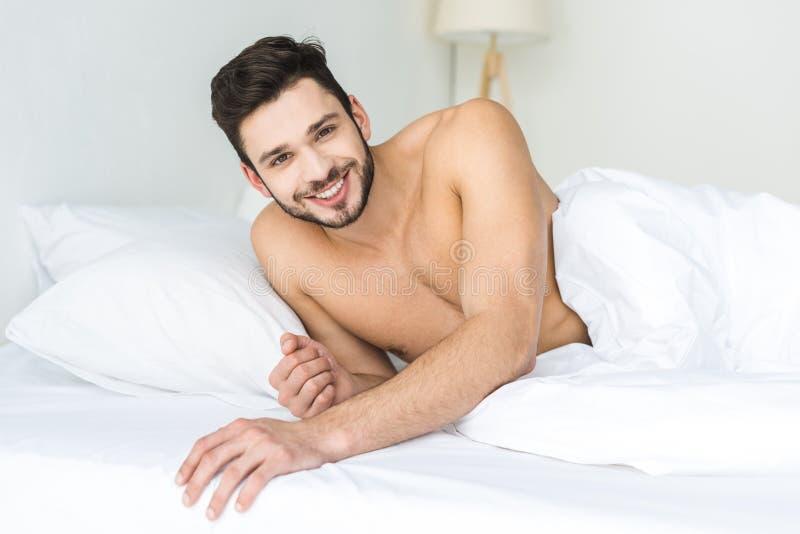 gladlynt shirtless man som kopplar av i säng arkivfoton