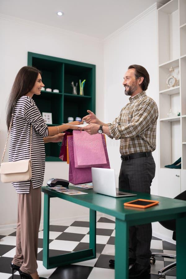 Gladlynt shoppa arbetaren som ger de shoppa påsarna till en kund arkivfoto