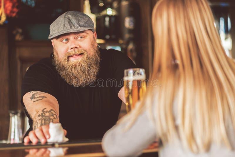 Gladlynt skäggig fet bartender som playfully ser klienten arkivfoto
