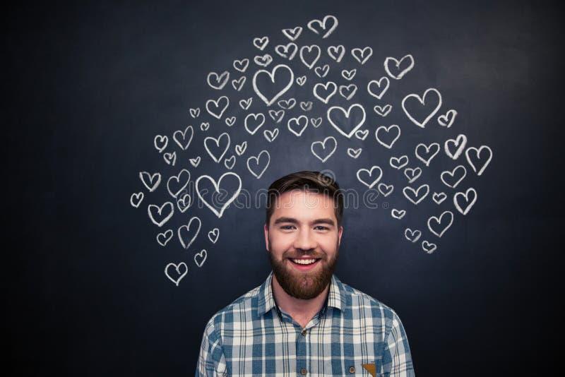 Gladlynt skäggig man med hjärtor på svart tavlabakgrund royaltyfri bild