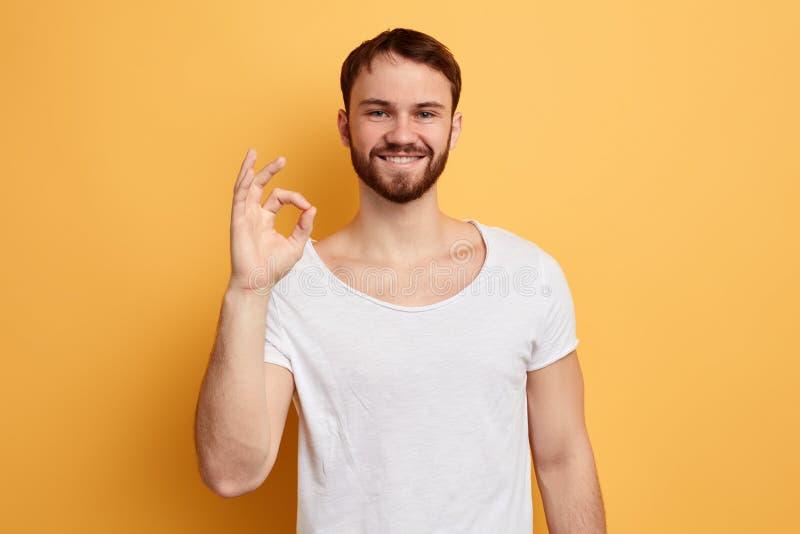 Gladlynt skäggig man som visar den ok gesten som isoleras på den gula bakgrunden fotografering för bildbyråer