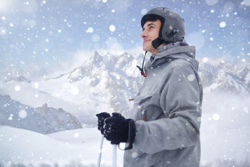 Gladlynt skidåkare som ser avlägsen, innan att starta till att skida Lycklig man som tycker om ferie i vintersäsong Le bergsbesti royaltyfria bilder
