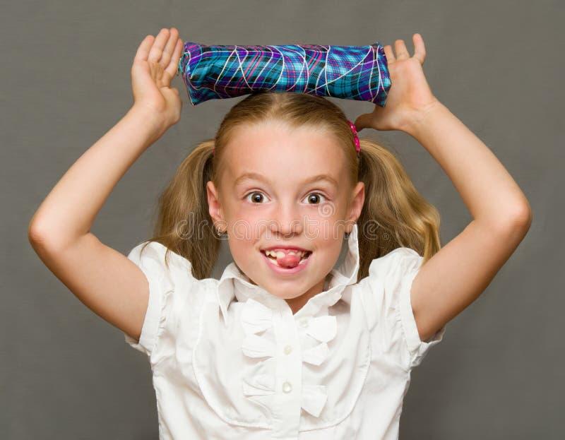 Gladlynt skolflicka med blyertspennafallet. arkivfoton