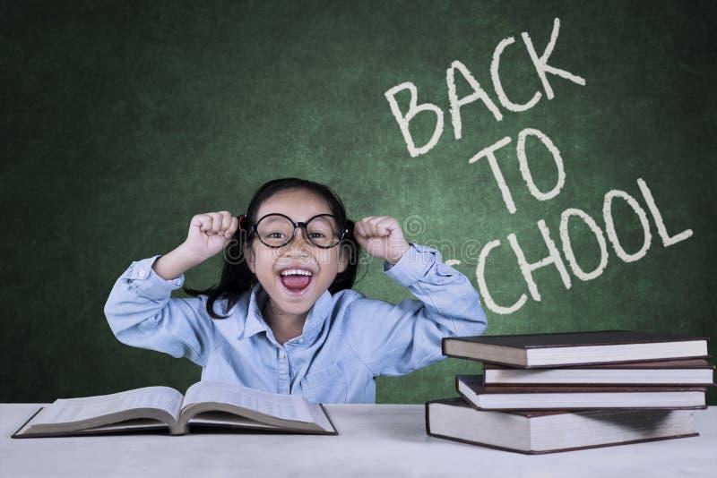Gladlynt skolflicka med tillbaka till skolaordet arkivfoton