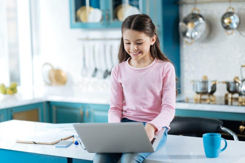 Gladlynt skolflicka som arbetar på hennes bärbar dator royaltyfri foto