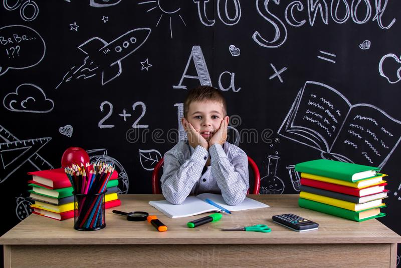 Gladlynt skolpojkesammanträde på skrivbordet med böcker, skolatillförsel, med båda armar under cheecksna royaltyfri fotografi