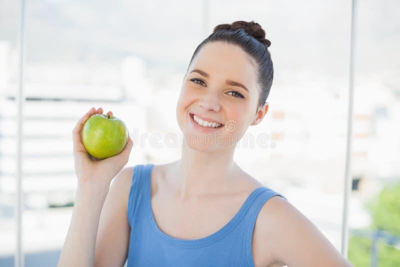 Gladlynt spenslig kvinna i äpple för sportswearinnehavgräsplan royaltyfri bild