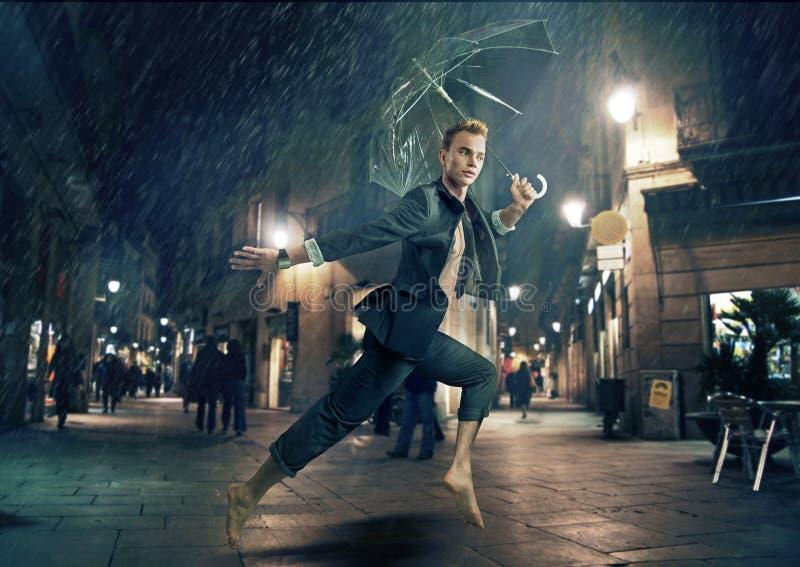 Gladlynt spring för ung man under regnigt väder royaltyfri fotografi