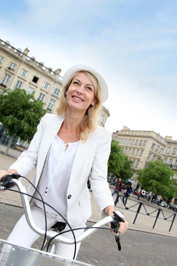 Gladlynt stående av den medelåldersa kvinnan på stadscykeln royaltyfri bild