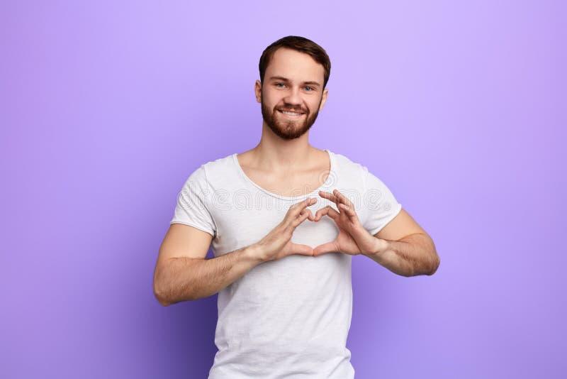Gladlynt stilig grabb som visar hjärtasymbol och form med händer Romantiskt begrepp fotografering för bildbyråer