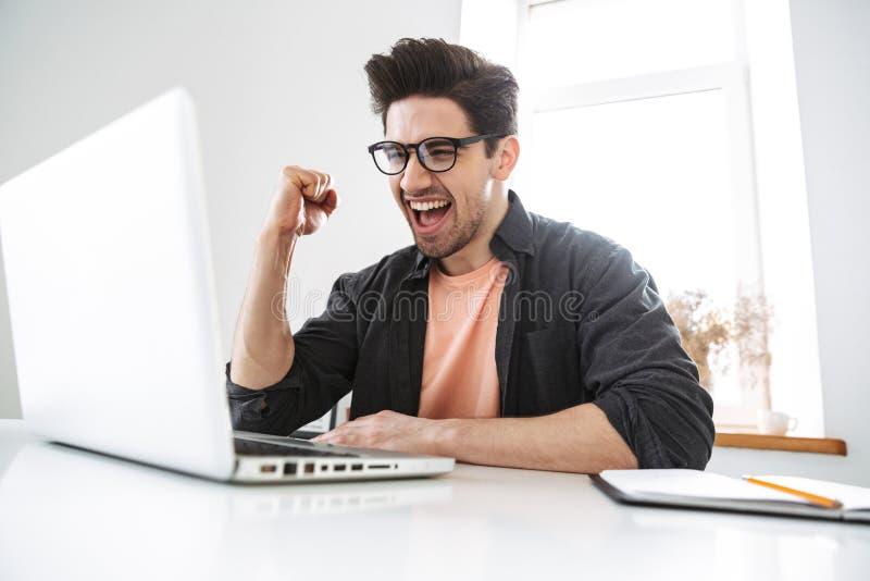 Gladlynt stilig man i glasögon genom att använda bärbar datordatoren royaltyfri bild
