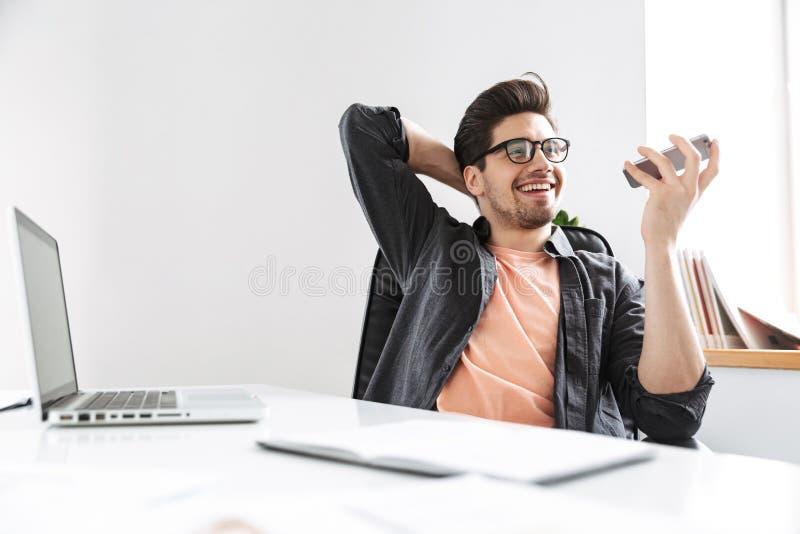 Gladlynt stilig man i glasögon som talar vid smartphonen arkivfoto