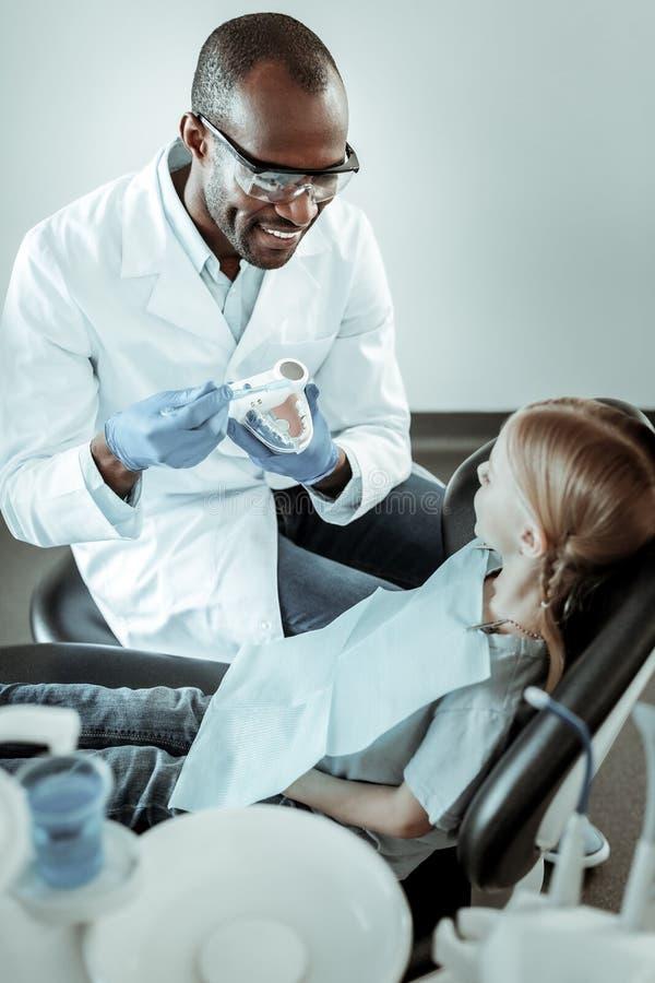 Gladlynt stomatologist som visar den högra vägen av att borsta för tänder arkivfoto