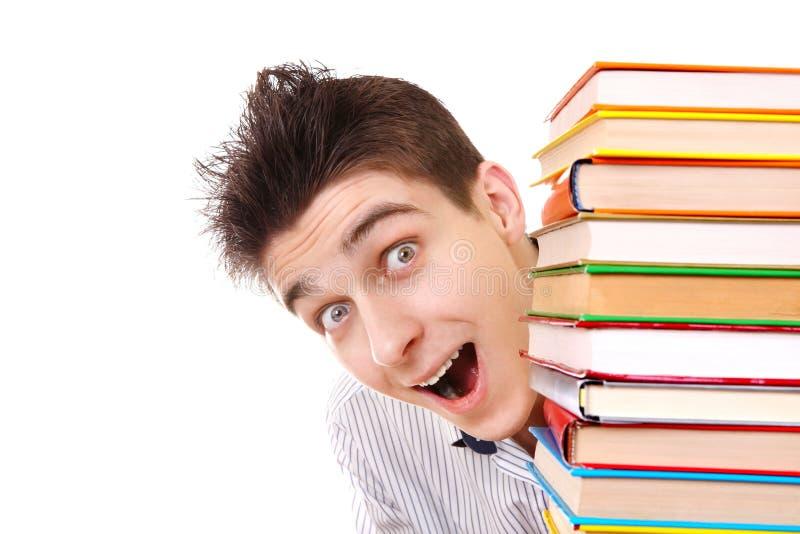 Gladlynt student bak böckerna arkivfoton