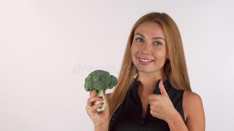 Gladlynt sund härlig kvinna som rymmer broccoli som visar upp tummar royaltyfri fotografi