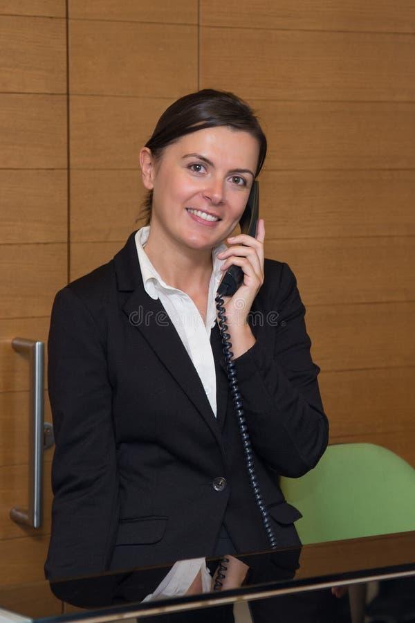 Gladlynt svara för receptionist arkivfoto