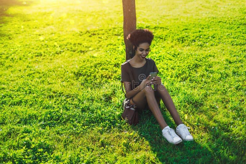 Gladlynt svart flicka med mobiltelefonsammanträde på gräset arkivfoto