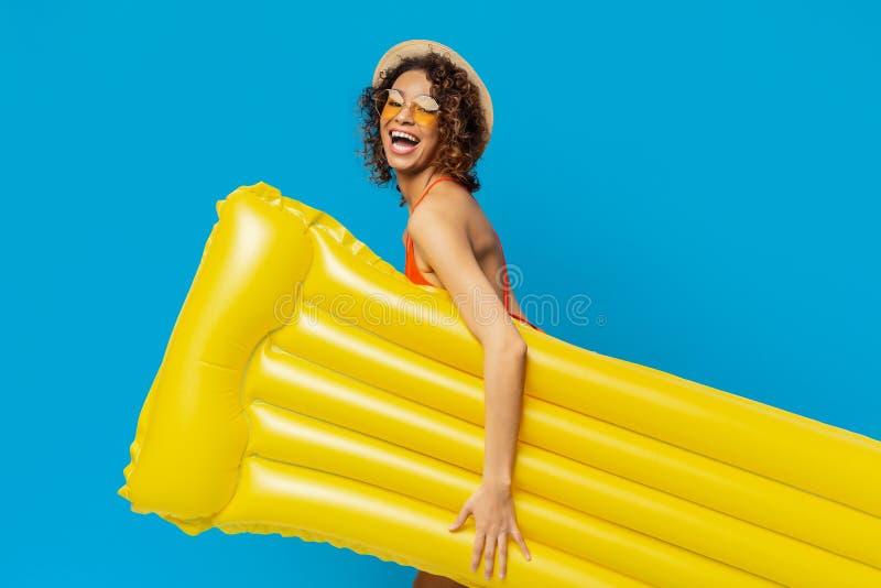 Gladlynt svart flicka som går att samla med den gula uppblåsbara madrassen royaltyfria foton