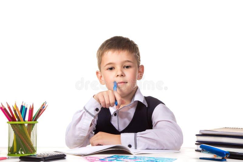 Gladlynt tillfredsställt fundersamt le elevsammanträde på skrivbordet på den vita bakgrunden fotografering för bildbyråer