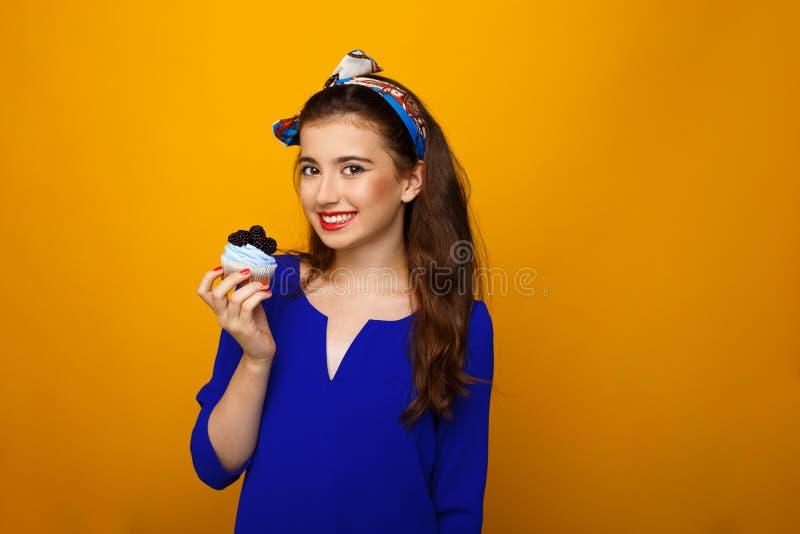 Gladlynt tonårig flicka i färgrik kläder som tas i hand en muffin som ser kameran, över gul bakgrund kopiera avst?nd royaltyfri foto