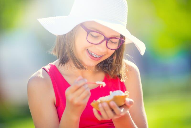 Gladlynt tonårs- flicka med tand- hänglsenexponeringsglas och glass Stående av en le nätt ung flicka i sommardräkt med is royaltyfri bild