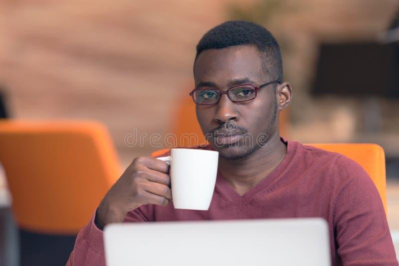 Gladlynt ung afrikansk affärsmanmaskinskrivning som ser på bärbara datorn royaltyfria foton