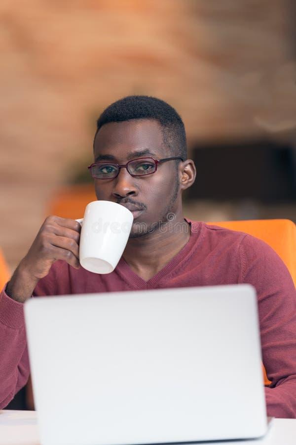 Gladlynt ung afrikansk affärsmanmaskinskrivning som ser på bärbara datorn arkivfoton