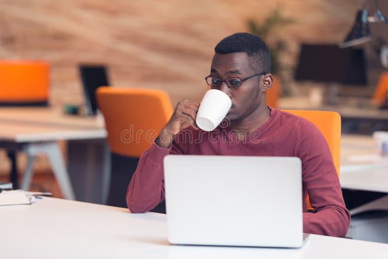 Gladlynt ung afrikansk affärsmanmaskinskrivning som ser på bärbara datorn royaltyfria bilder