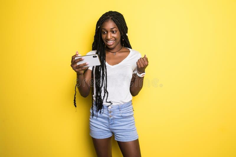 Gladlynt ung afrikansk amerikanflicka som använder mobiltelefonen, le som poserar på gul bakgrund royaltyfri bild