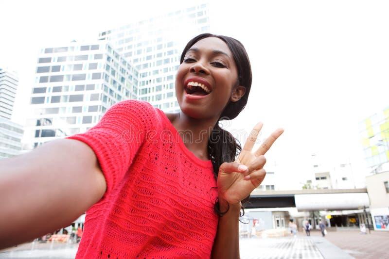 Gladlynt ung afrikansk amerikankvinna som tar selfie i staden royaltyfria bilder