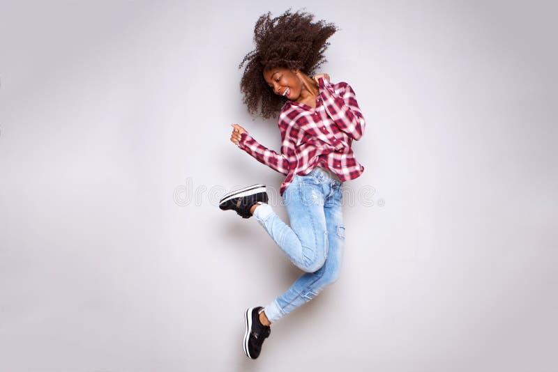 Gladlynt ung afrikansk kvinnabanhoppning för full kropp i luft över vit bakgrund arkivbild